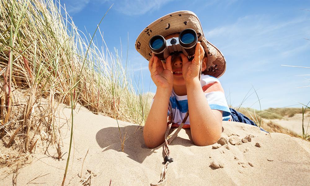 Photo of a boy using a pair of binoculars on a beach